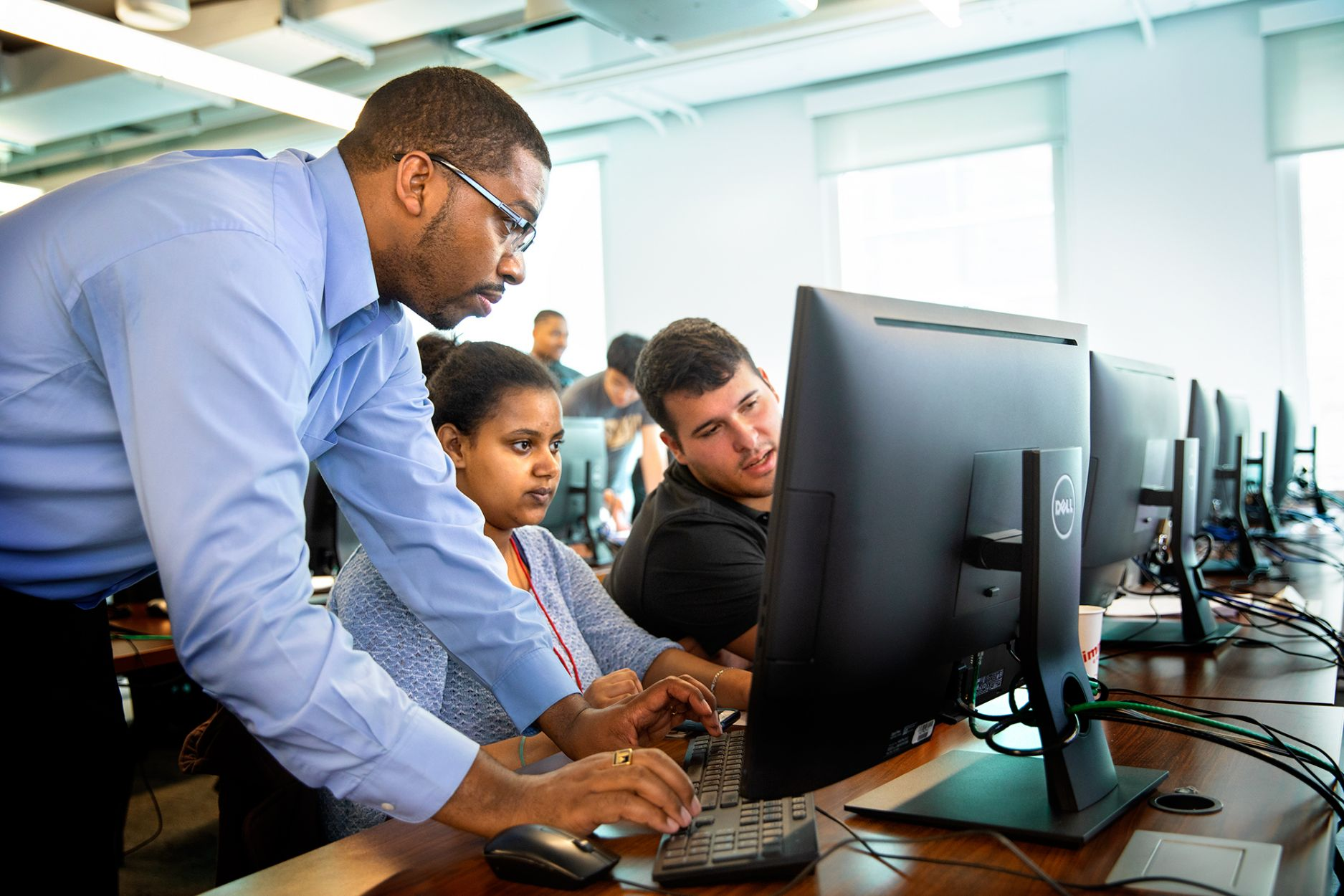 Hakim Weatherspoon, left, associate professor of computer science, helps students at the SoNIC summer workshop.