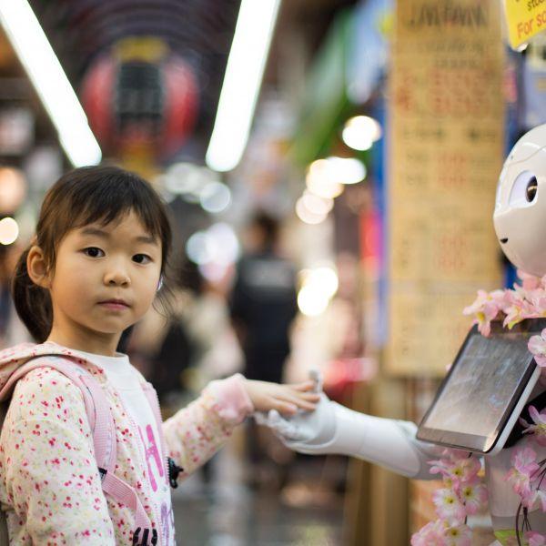 little girl holding hand of robot